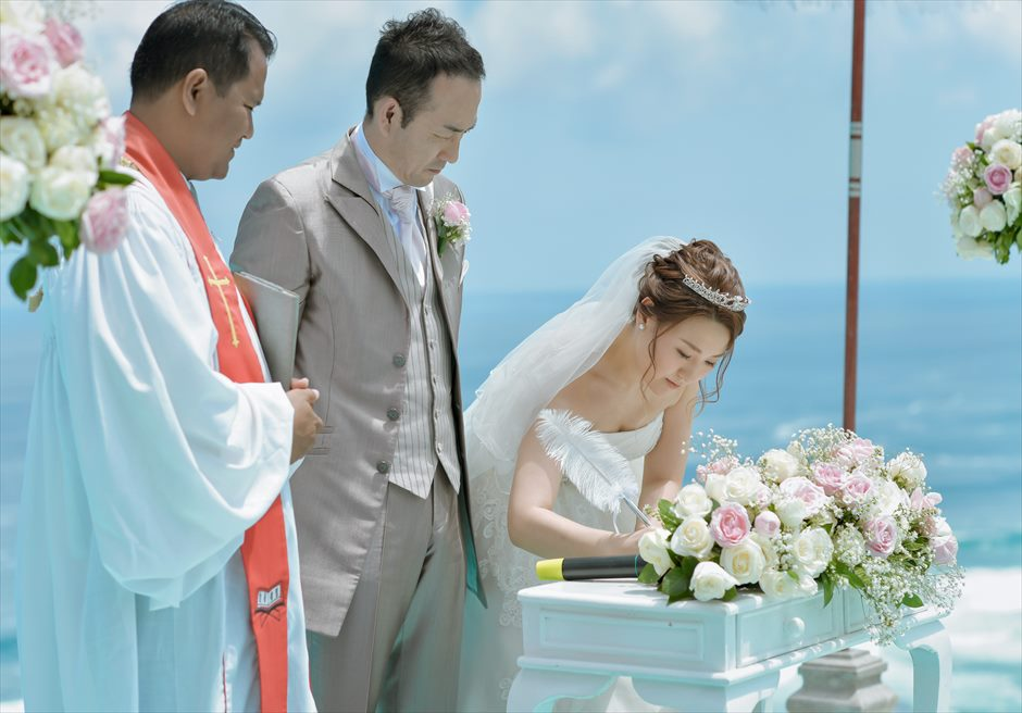 カルマ・カンダラ・ウルワツの大海を背景に結婚証明書にサイン